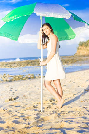 Woman Standing Under The Shade Of A Green And White Umbrella While On A Peaceful And Tranquil Vacation Of Leisure photo