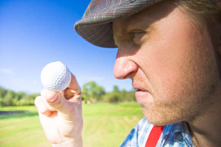 Upset Golfer Has A Mid Game Crisis While Arguing With The Golf Ball He Is Holding In A Funny And Humorous Sport Concept photo