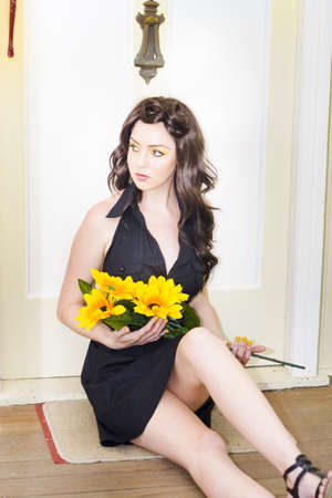 A Sad And Lonely Woman Locked Out In The Cold Sits In Solitude By A Front Door Holding Floral Sunflowers Waiting For Someone To Open The Door, In Romanic Hope Stock Photo - 12865308
