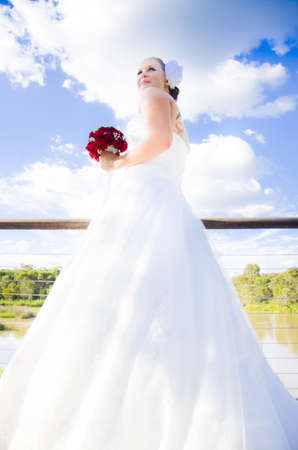 Down Up View On A Pensive Soon To Be Married Bride In White Wedding Dress Carring Flower Boquet Looking Ahead photo