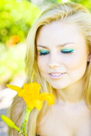 Stunning Blond Girl Standing In A Spring Orchid Smelling A Bright Yellow Flower While Taking Time To Smell The Flowers Stock Photo - 12807374