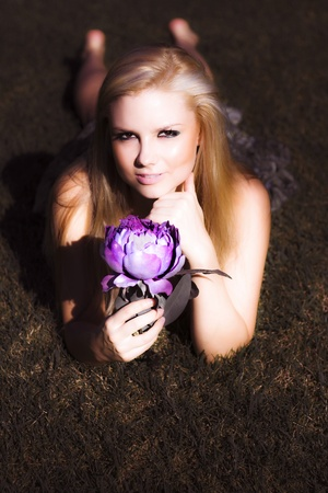 Sensual Blonde Holding Lotus Flower lying on her stomach on the grass in semi darkness photo