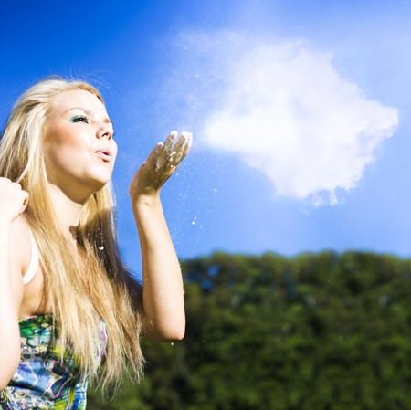 Cloud Creation With A Puff Of Magic, a beautiful blonde girl gently blows a puff of white dust into the blue sky in a creation concept Stock Photo - 12807390