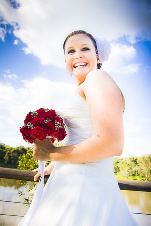 A Young Beautiful Bride Wearing A White Dress And Carrying Red Rose Bouquet With An Expression Of Complete Joy And Laughter On Her Wedding Day Against A Blue Sky Background photo