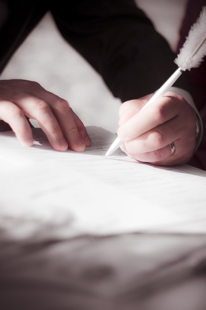 Focus On The Hands Of The Groom While He Signs The Marriage Certificate During His Wedding photo