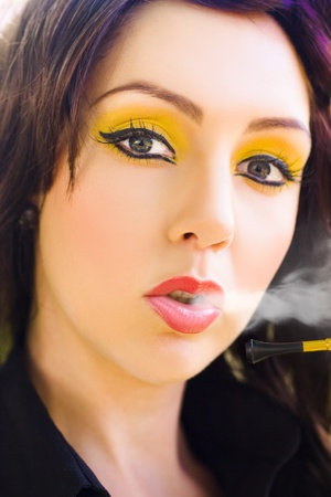 Face Of A Gorgeous And Stunning Young Brunette Woman In Retro Summer Makeup Blowing And Puffing Out Cigarette Smoke In A Glamour Smoking Style Portrait photo