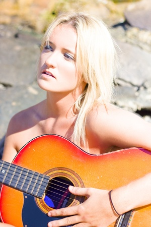 Close Up Of An Attractive Young Blonde Woman Composing A Song On A Musical Instrument Or Guitar In A Beach Music Image photo
