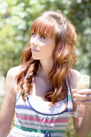 Half Body Portrait Of Attractive Young Woman With Auburn Hair And Glass Of Champagne Leafy Trees In Background Stock Photo - 12864976