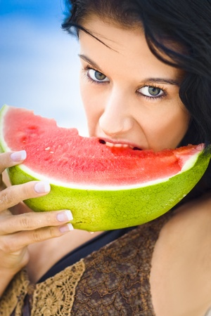 Beautiful Young Female With Black Hair Biting Into Juicy Pink Watermelon With A Feisty Expression Of Hunger And Desire With Blue Sky Background Stock Photo - 12863770