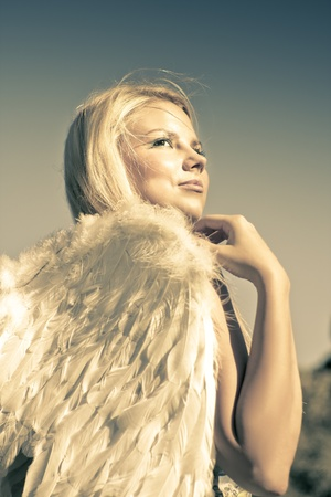 Golden Female Angel Wearing White Feather Wings While Looking To The Heavens Above In A Depiction Of Faith And Belief Stock Photo - 12807514