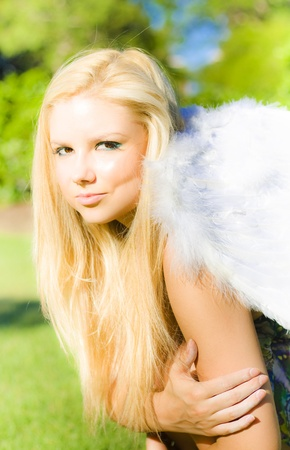 Blonde Angel. Smiling pretty blonde angel girl with feathery wings in a park, closeup soft portrait Stock Photo - 12807527