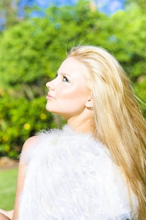 Cupid, The Goddess Of Love, Beautiful young blonde woman in a green park wearing fluffy white feathered wings conceptual for Cupid the Goddess Of Love. Stock Photo - 12807574