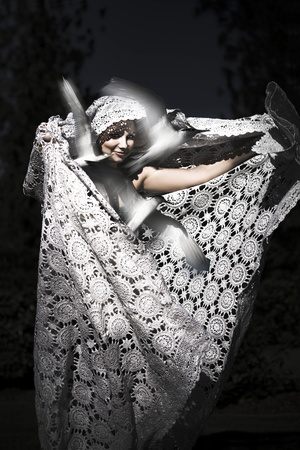 Silver Seductress On Black, dramatic portrait of a beautiful woman draped in flowing patterned shawl releasing birds in a freedom concept Stock Photo - 12807618