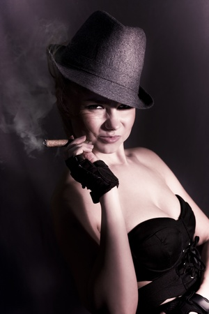 Shadowy Underworld Portrait Of A Striking Woman Wearing Detective Hat Smoking A Fat Cigar With A Cheeky Mysterious Grin In The Black Shadows Of Darkness Stock Photo - 12807509