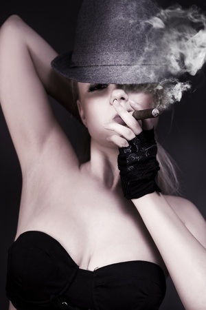 Low angle portrait of a glamorous female private eye puffing on a large cigar with a hat cocked over one eye. photo