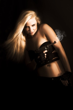 Female James Bond Concept. Provocative sexy blonde operative in retro skimpy outfit and toting a smoking handgun highlighted in the shadows Stock Photo - 12807300