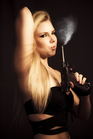 Hot Shot Concept. Gorgeous blonde woman blowing at the wisp of smoking coming from her smoking handgun with a seductive expression photo