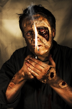 Dead Man Smoking. Conceptual image of a living dead man, or zombie, with decaying flesh smoking a cigarette photo