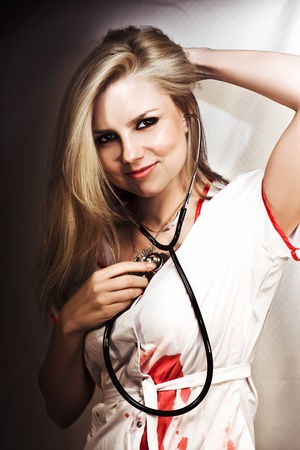 Beautiful smiling young blonde nurse holds a stethoscope to her heart in a concept of being love struck. photo