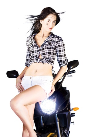 Sexy young woman in shorts posing on the handlebars of a motorbike with its headlamp shining photo