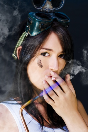 Female mechanic on smoko holding an acetylene flame and smoking a cigarette against its blue flame in a rough tough female conceptual photo