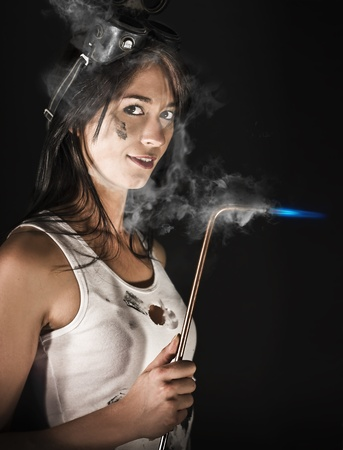 Lady Boilermaker At Work. Closeup of an attractive girl wearing safety goggles and holding a burning acetylene torch against a dark bakground. photo