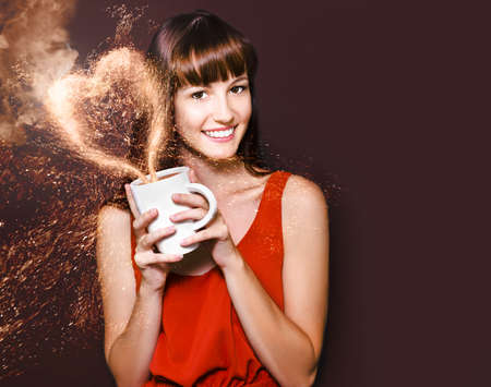 cafe copyspace concept of a smiling pretty woman holding a steaming cup of hot coffee with a heart forming in a splash above in a image titled i love hot coffee photo
