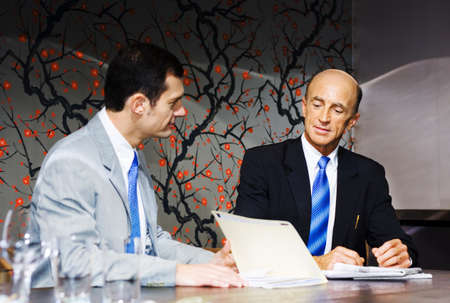 A Team Of Two Executive Business People Plan And Develop Future Business Growth While Looking Through Files And Documents During A Boardroom Meeting photo