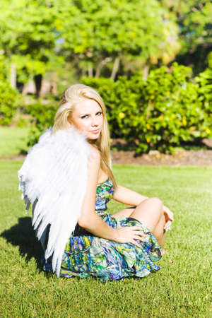 Beautiful young celestial angel in white wings seated on the grass looking back over her shoulder at the camera with a gentle expression Stock Photo - 12876063