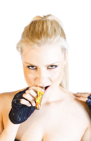 Blonde firery woman with evil flame eyes wearing a black mitt smokes a fiery cigar in a devilish representation of a blonde demon Stock Photo - 12863170