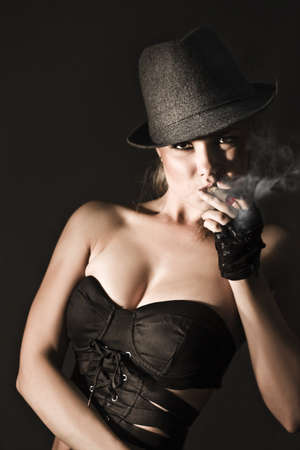 Moody underworld portrait of a sexy voluptuous woman with a hat pulled low over her brow smoking a cigar in a female gangster concept Stock Photo - 12863415