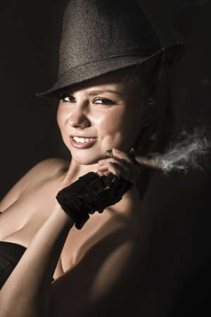 Playful photograph of a vintage 50s broadway dancer holding cigar on a dark background photo