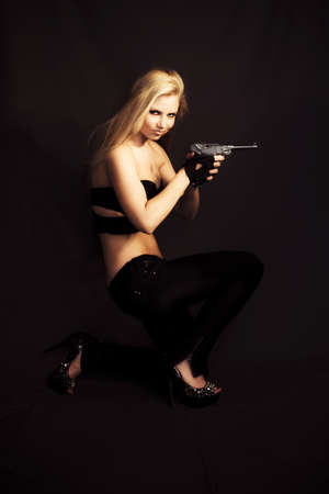 Sexy blonde lurking in the shadows with a handgun cocked and ready in a private investigator or assassin concept Stock Photo - 12863158