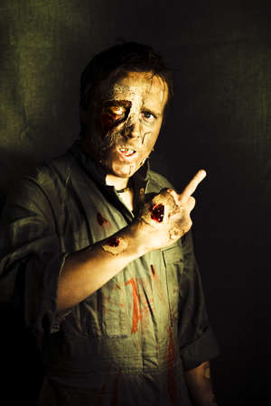 A walking dead zombie with decaying and rotting flesh gives a fingers up sign marking or singling out a person for their demise in a death threat concept Stock Photo - 12875714