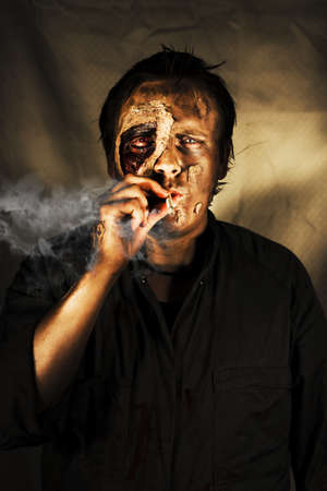 Decaying zombie smoking a cigarette in a conceptual image of what can happen to someone who cannot kick the habit Stock Photo - 12874849