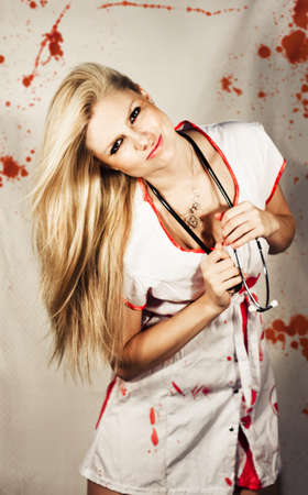 A smiling sexy nurse in a bloodstained uniform in front of blood spattered curtains in an inhospitable hospital horror concept photo