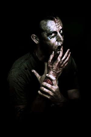 A decaying zombie feeds on a severed bloody human hand in the darkness of midnight in a deadly midnight snack conceptual photo