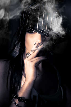 Face Of A Mysterious Urban Woman In Striped Cap Standing In The Shadows Of Darkness Smoking A Cigarette In A Sneak Smoke Conceptual, Focus On Cigarette Ash photo