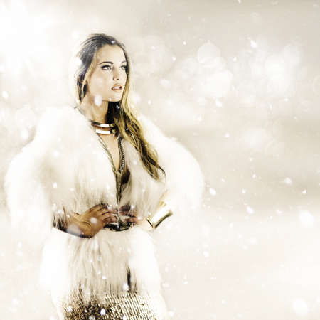elegant woman wearing fur coat with hands on hips, with snow falling around her in a winter weather concept Stock Photo - 12875266