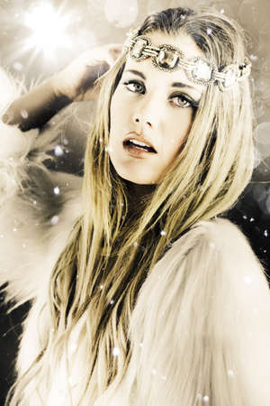 Artistically toned image in cool tones of a beautiful blonde woman in white with a jewelled headband standing under falling snowflakes during winter in a enchanting snow princess concept photo