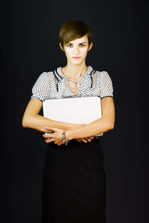 Pretty young woman on a dark background looks at the camera with trepidation as she clutches a briefcase to her chest in a new employee concept Stock Photo - 12863645