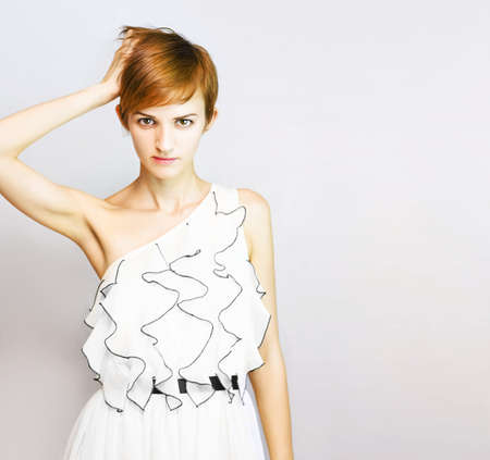 short haired woman wearing white dress with ruffles dress right hand touching head on a grey background with space for text Stock Photo - 12863424
