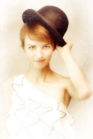 Textured sepia vintage portrait of a young woman with auburn hair doffing her bowler hat in goodwill greeting gesture photo