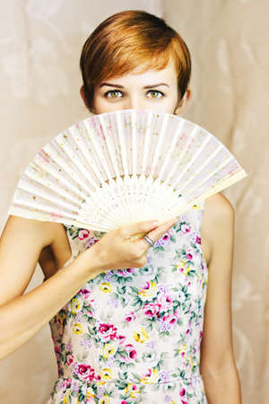 short-haired girl wearing a floral dress covering her mouth with a oriental fan in a beautiful secret conceptual Stock Photo - 12875818