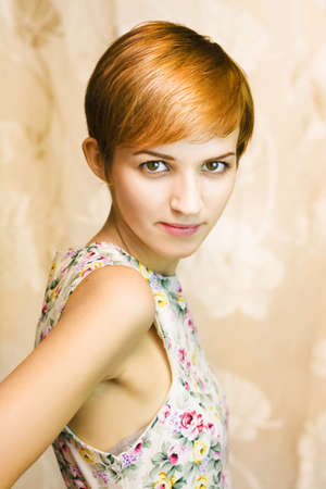 short haired girl in floral dress, body away from camera, right hand behind her on a floral brown background Stock Photo - 12874913