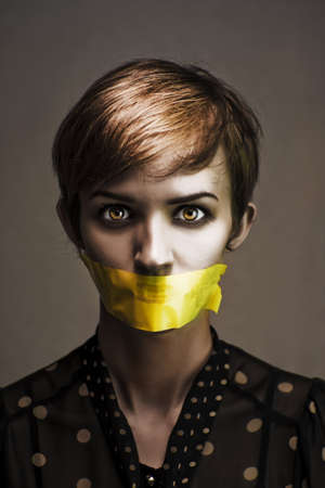 Dark Headshot Of A Distressed And Oppressed Woman Bound And Gagged In Silence With Yellow Masking Tape Covering Her Mouth In A Speak No Evil Conceptual photo