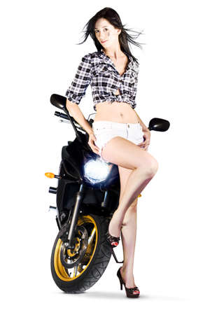 woman in white short short and black plaid shirt exposing her midriff leaning on a motorbike with headlight on photo
