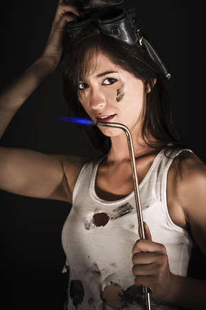 Dark portrait of a sexy young brunette woman in an oil-stained top and goggles holding a burning blow torch in a panel beater concept photo