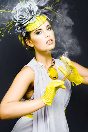 Woman in haute courure fashion outfit stubs out a newly lit cigar on her glove in an Out Of Time concept photo