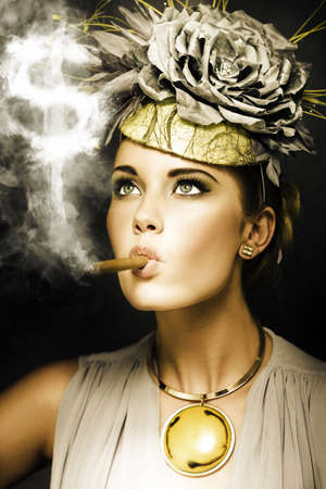 Wealthy woman in haute couture and ostentatious jewellery smoking a big fat cigar, conceptual of wealth and riches photo